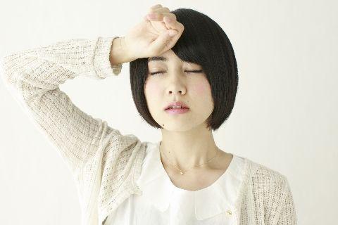 頭に手の甲をあててだるそうに目を瞑っている女性
